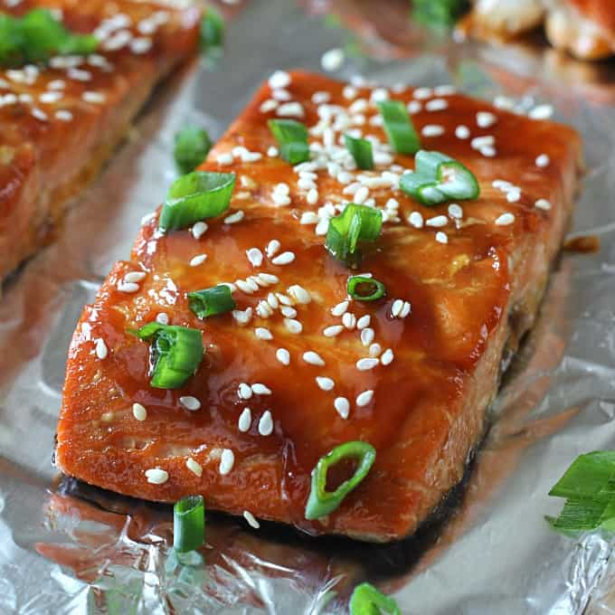 A close up of salmon with a glaze, sesame seeds, and green onions on top