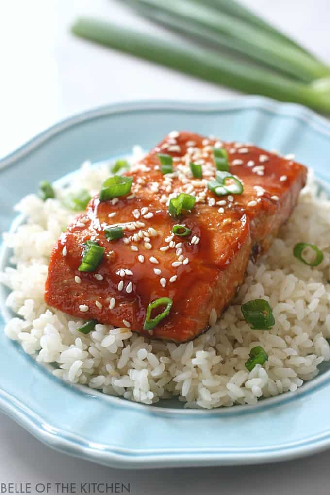 A close up of salmon with a glaze, sesame seeds, and green onions on top of rice