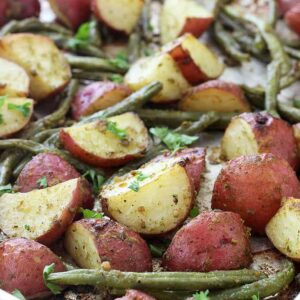 A close up of Pesto and Potatoes with green beans on a sheet pan