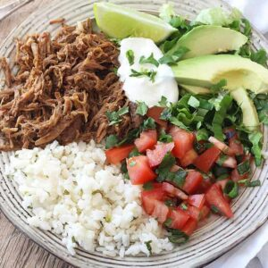 A plate of food with rice and vegetables, pork, lime, sour cream, and avocado