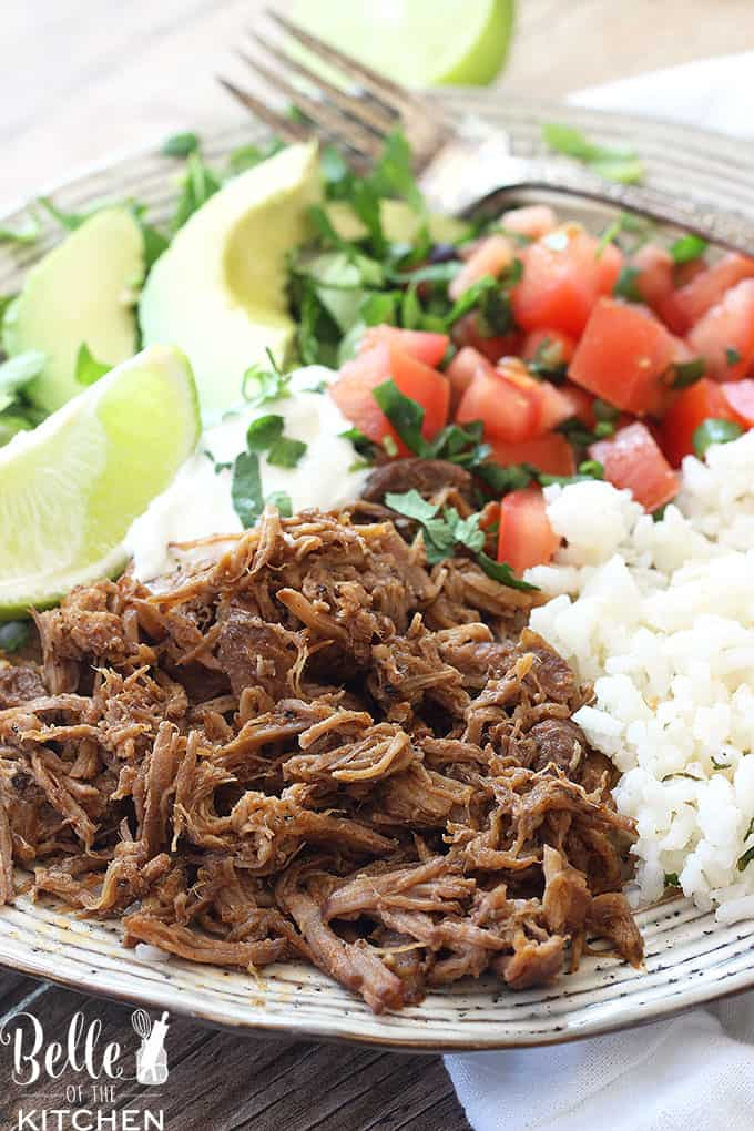 A plate of food with rice meat and vegetables, with Pork, sliced lime, and avocado