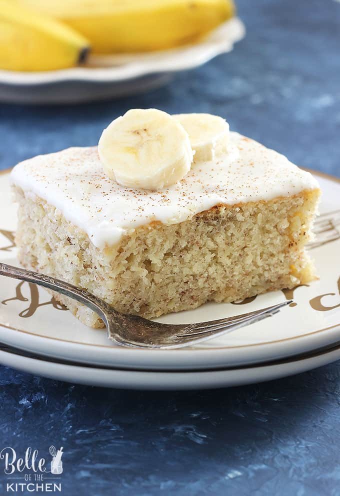 A piece of cake on a plate with bananas on top and a fork on the side