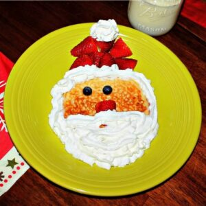 A plate with pancakes that look like Santa with fruit and whipped cream
