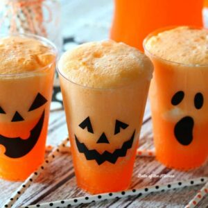 cups filled with Fanta, vanilla ice cream, and jack o'lantern faces on the side of the cups