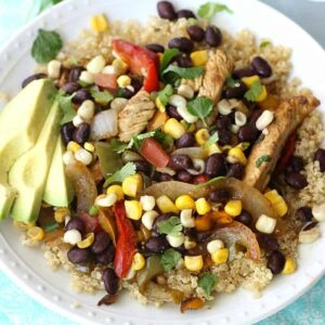 A plate full of food, with Chicken, Quinoa, avocado, black beans, onions, corn, and peppers