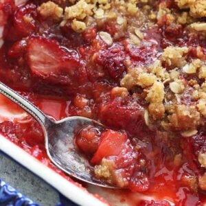 A close up of a bowl of food, with strawberry crisp and a spoon