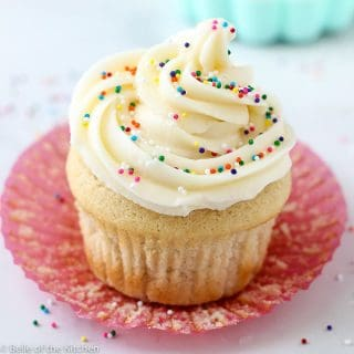 A close up of a vanilla cupcake with sprinkles on top