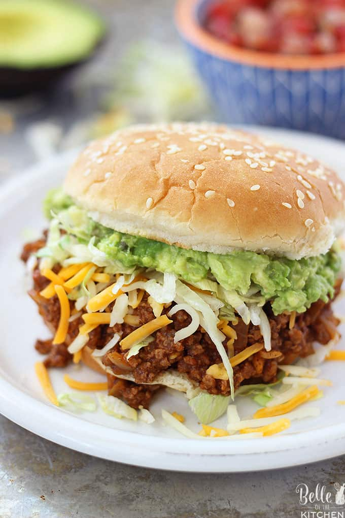 These Taco Sloppy Joes are the perfect mix of two dinnertime favorites! They are quick, easy to make, and a total crowd pleaser. Load them up with your favorite toppings and serve for an awesome dinner or for parties and tailgates! #sloppyjoes #dinner #groundbeef #tacos #tacotuesday