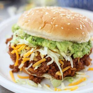 A sloppy Joe sandwich with lettuce and cheese on a plate