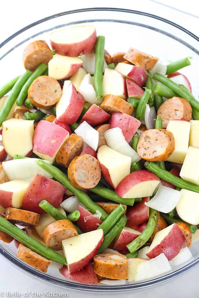 A bowl of chopped sausage, potties, onions, and green beans