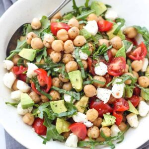A bowl of salad on a plate with Chickpea and Avocado