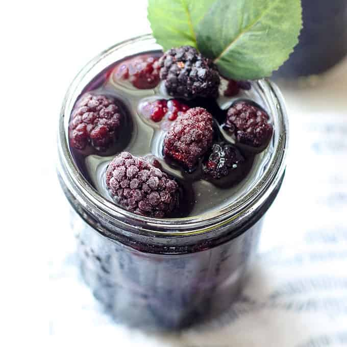 mason jar filled with blackberry sweet tea and frozen blackberries