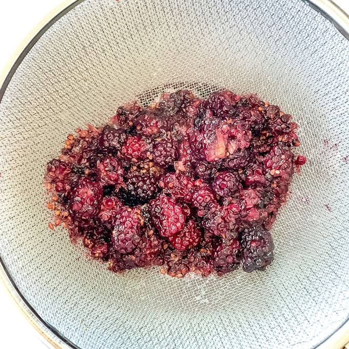 a strainer filled with blackberries