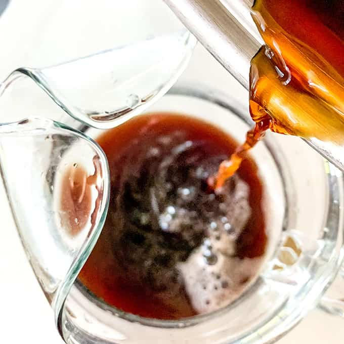 tea being poured into a pitcher
