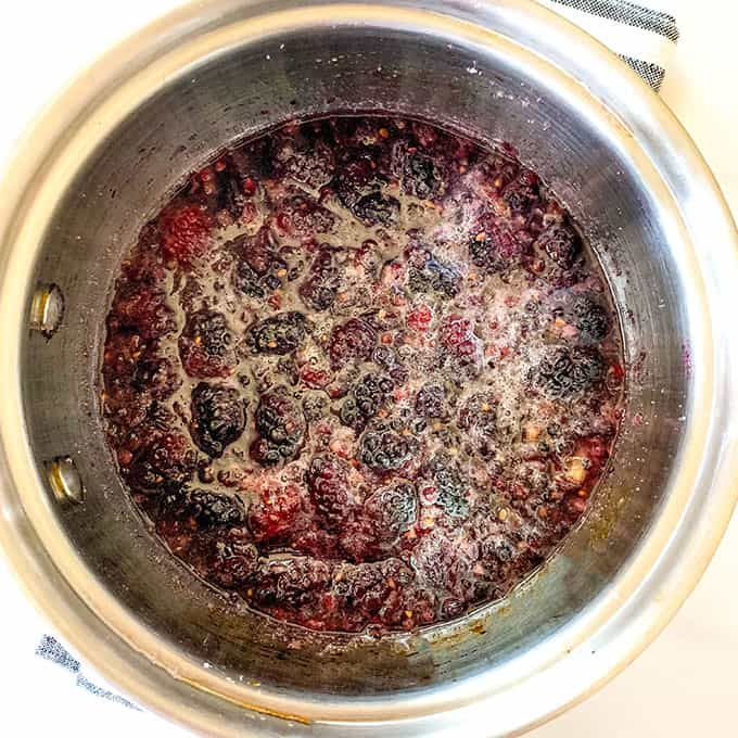a pan filled with blackberries being cooked
