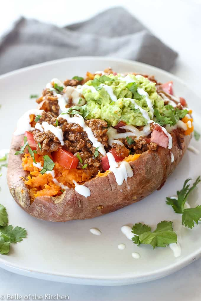 sweet potato filled with taco toppings on a white plate