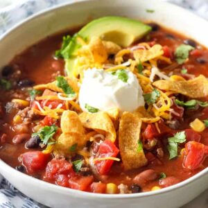 A bowl of taco soup with sliced avocado and sour cream