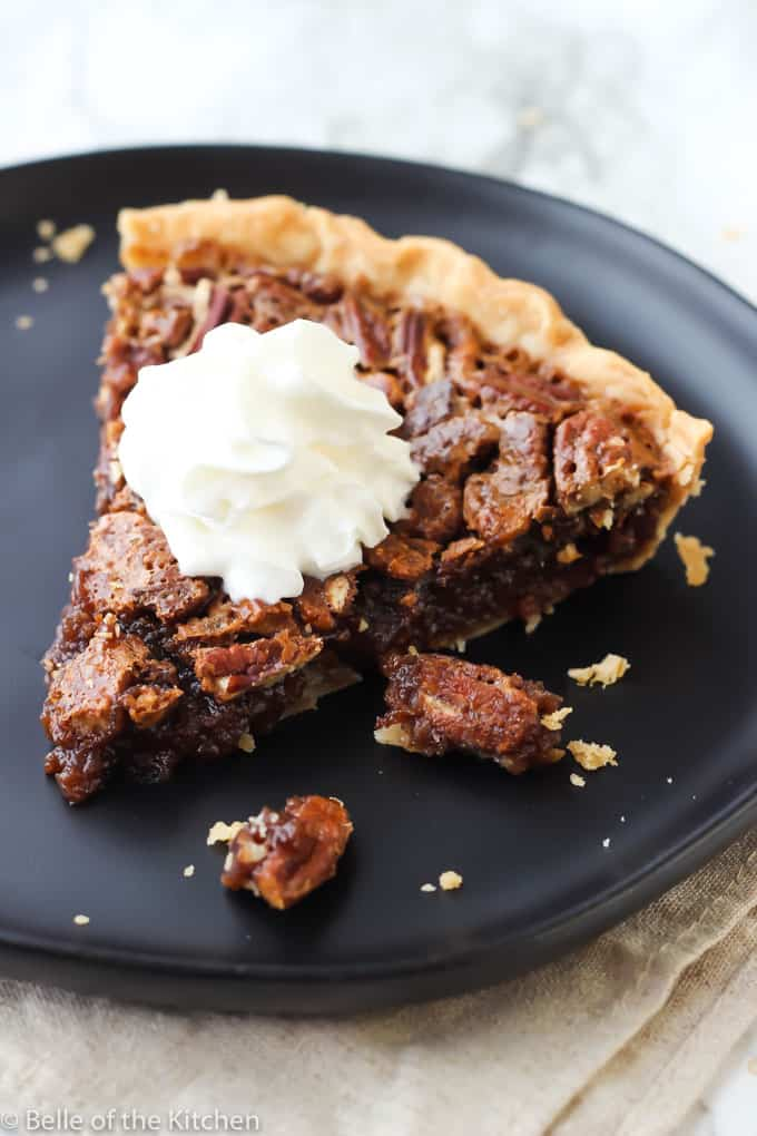 A piece of Chocolate Pecan Pie on a black plate