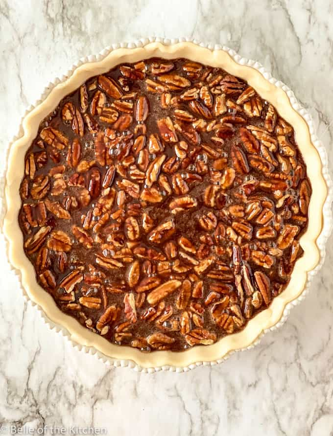 A close up unbaked chocolate pecan pie