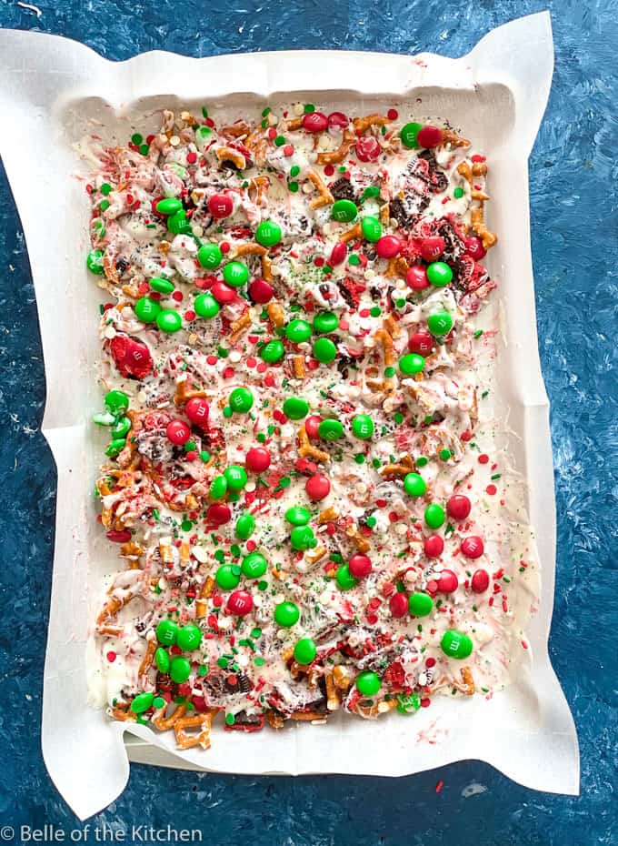 sheet pan with cookie bark made from M&Ms, pretzels, Oreos, almond bark, and sprinkles