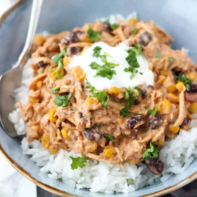 blue bowl with white rice topped with shredded chicken, cream cheese, black beans, corn, salsa, with sour cream and cilantro on top