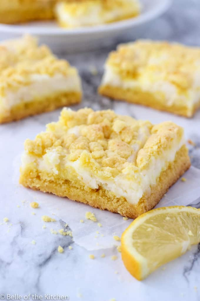 white background with sliced lemon cheesecake bars