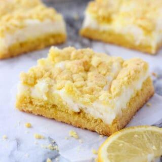 Slices of lemon cheesecake bars with sliced lemon on the side