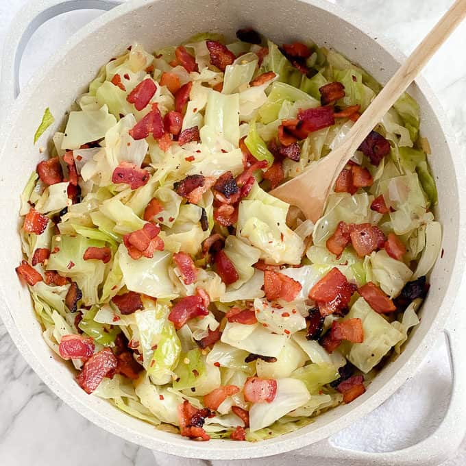 aerial shot of dutch oven with chopped cabbage and bacon