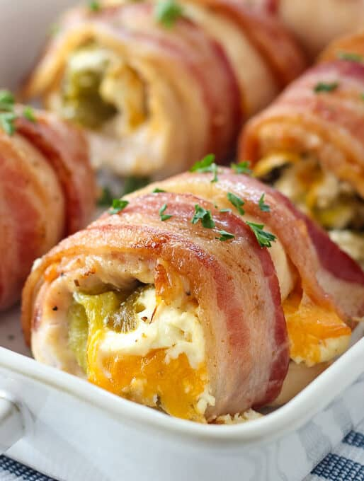 a white baking dish filled with chicken breasts wrapped in bacon