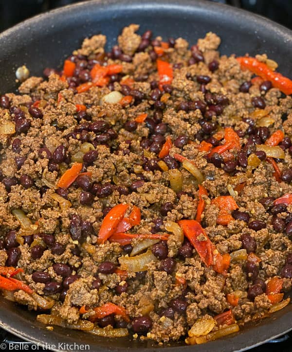 nonstick skillet with cooked ground beef, black beans, onions, and red pepper
