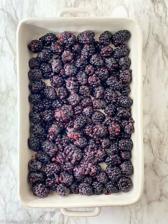 a rectangle baking dish full of blackberries