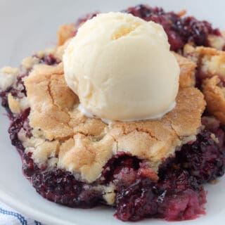 a plate with blackberry cobbler and vanilla ice cream on top