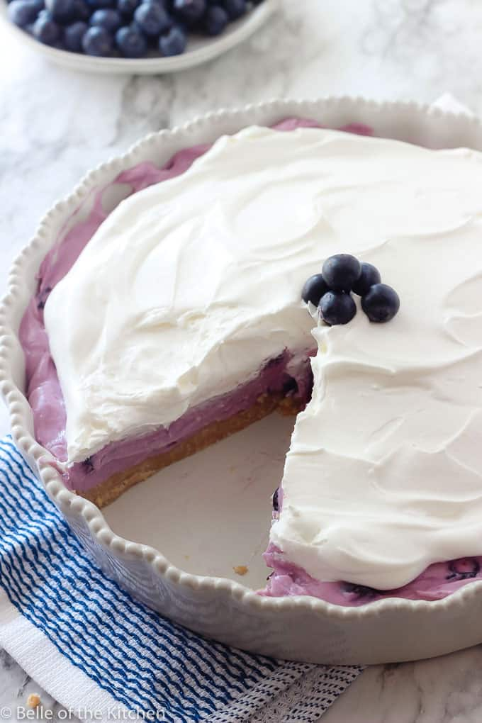 blueberry pie with whipped topping with a slice taken out