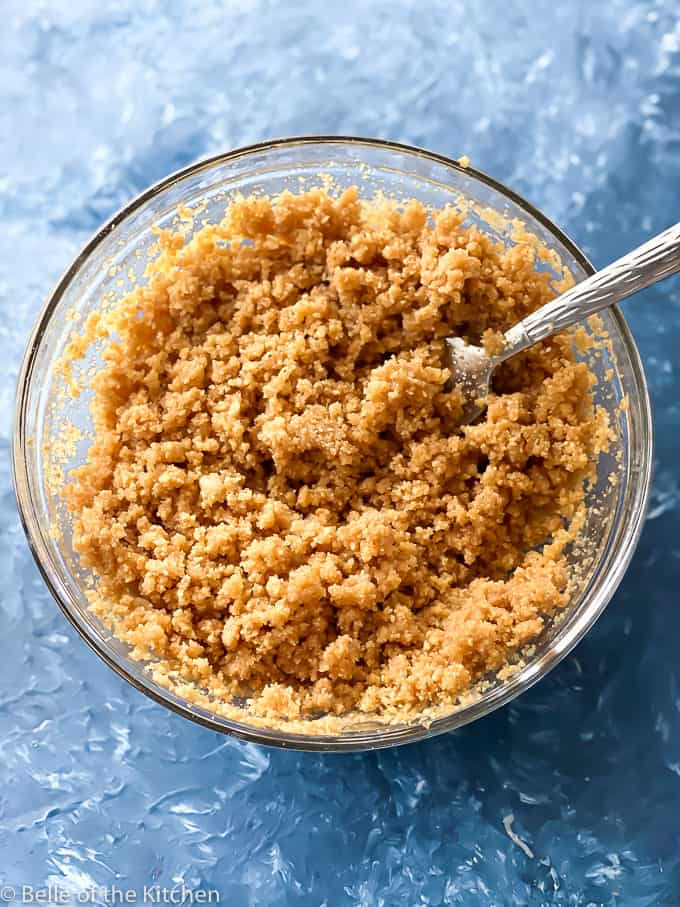 glass bowl with graham cracker crumbs and melted butter