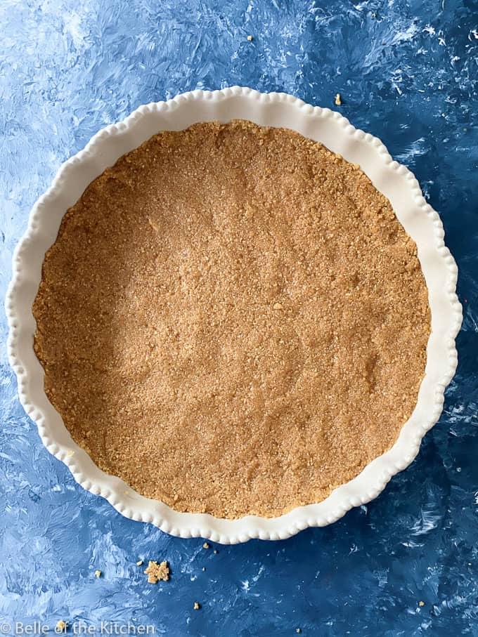 graham cracker crust in a white pie plate