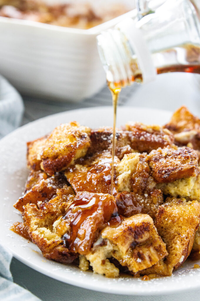 a white plate with french toast casserole and syrup poured over the top
