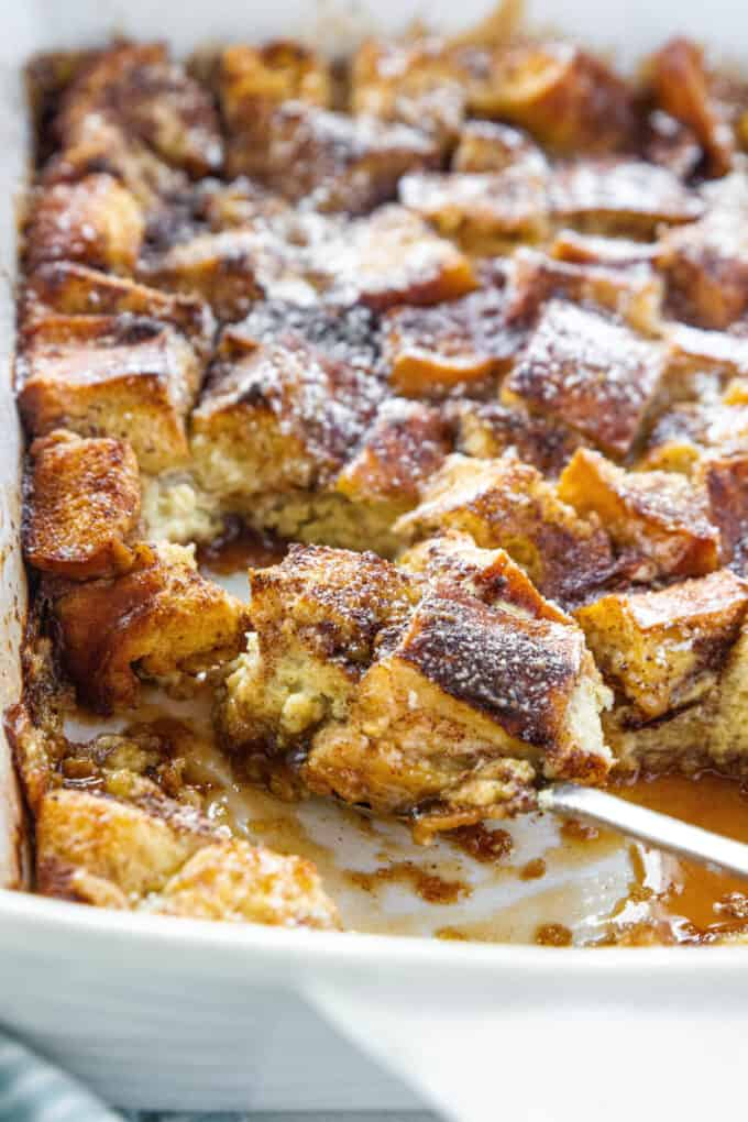 a white baking dish full of french toast casserole with a spoon