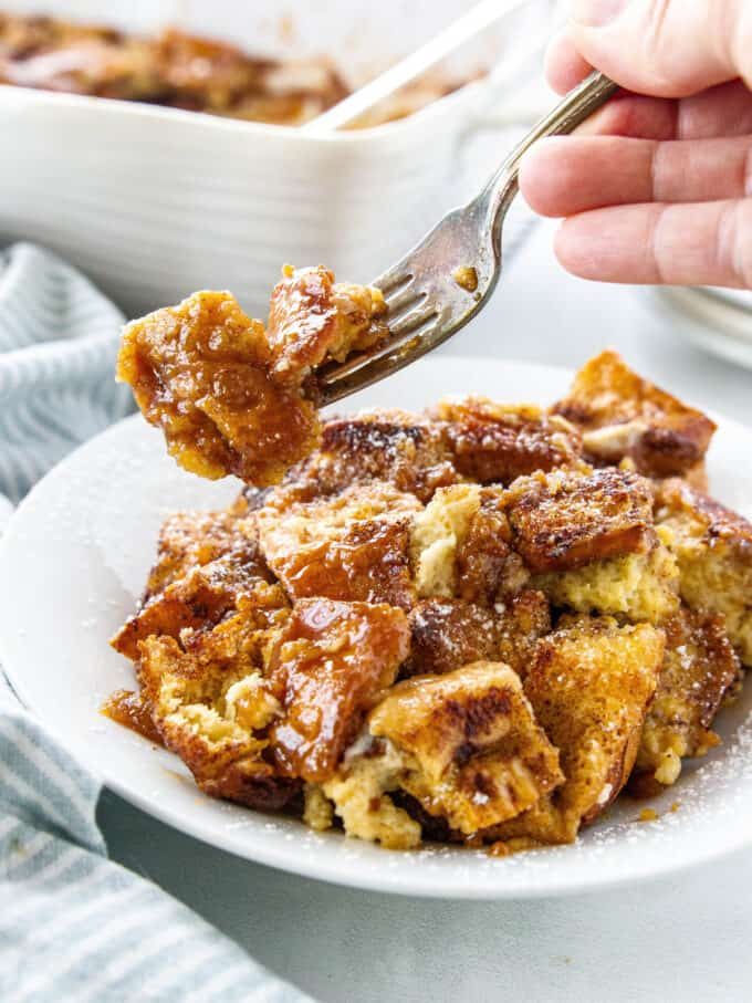 a white plate with french toast casserole and a fork holding a small portion
