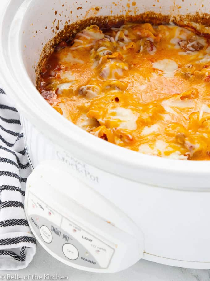 a white crockpot filled with cheesy tortellini