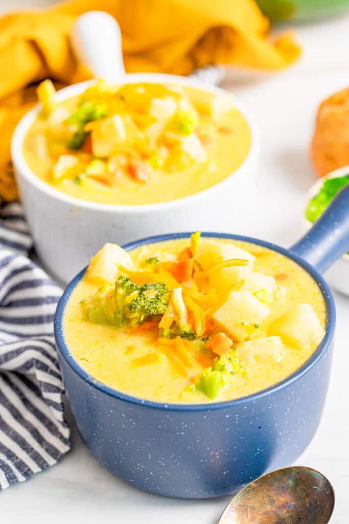 blue bowl full of cheesy chowder topped with vegetables