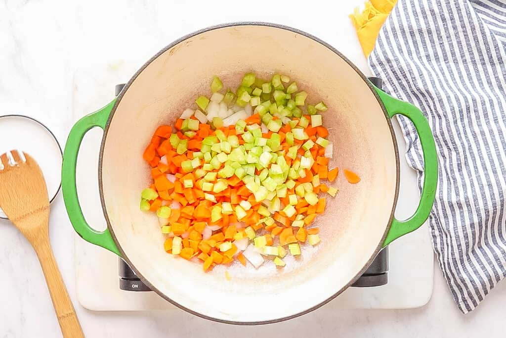 a large pot full of diced carrots, onions, and celery