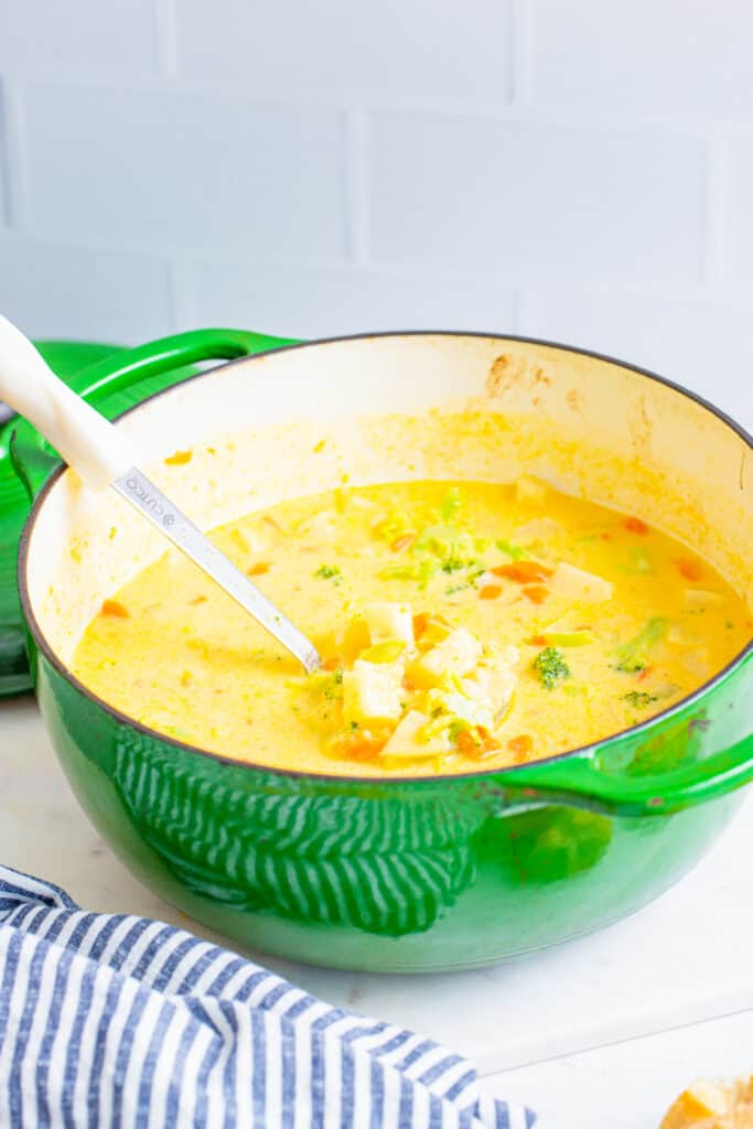 a large pot full of cheesy vegetable chowder with a ladle scooping some out