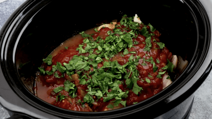 a crockpot bowl with chicken, salsa, lime, and cilantro
