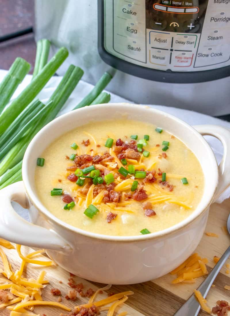A bowl of potato soup with a spoon topped with bacon, cheese, and green onions