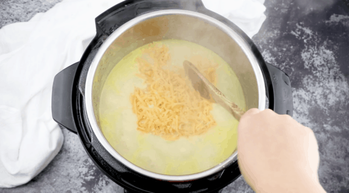 a wooden spoon stirring cheese into potato soup in an Instant Pot