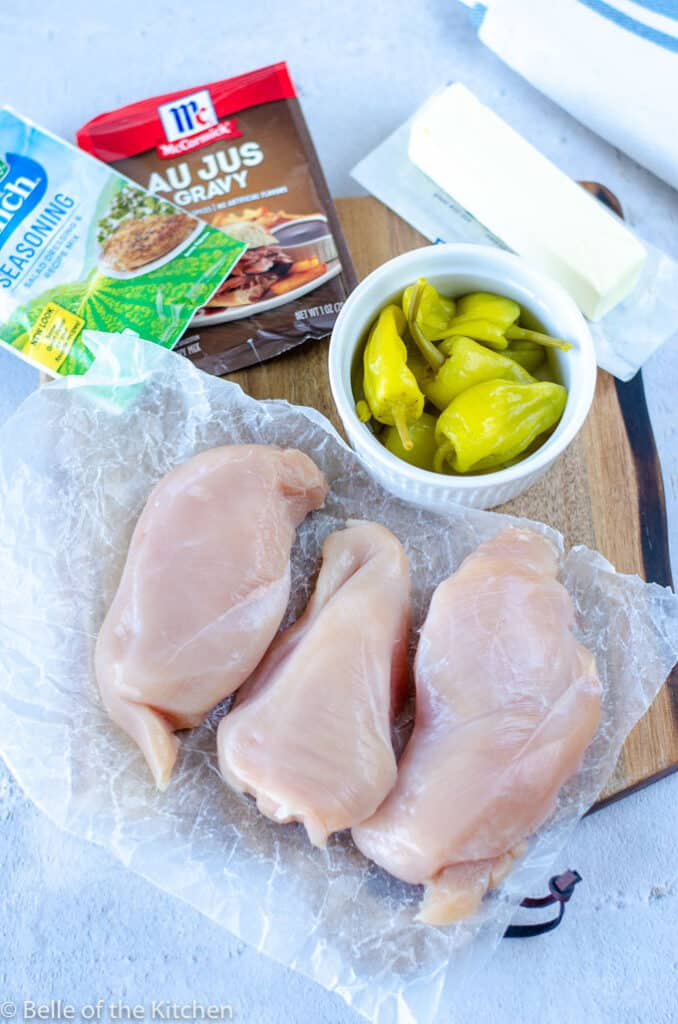 chicken breasts, seasoning packets, and a bowl of peperoncini peppers on a wooden cutting board