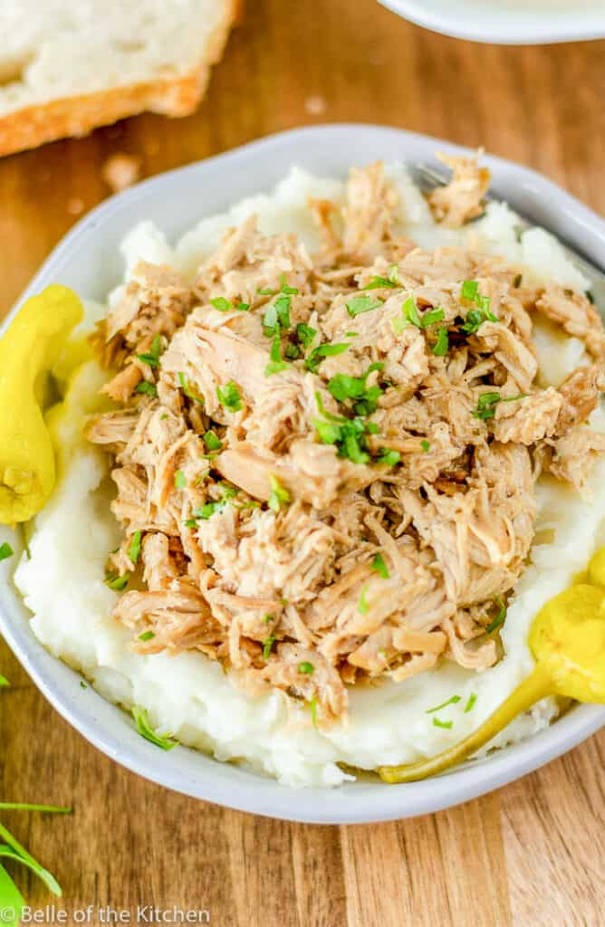 white bowl filled with mashed potatoes and shredded Mississippi chicken