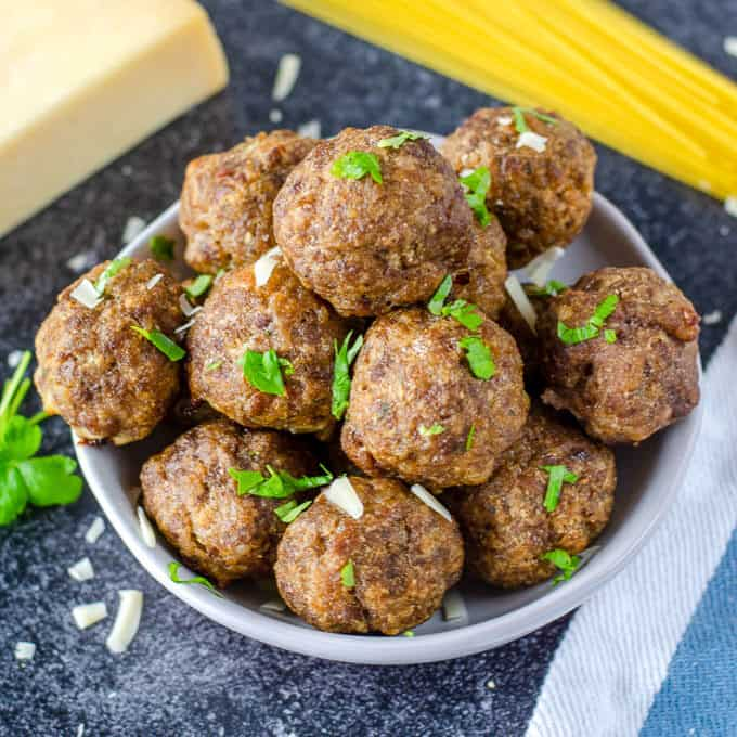 a white bowl filled with baked meatballs