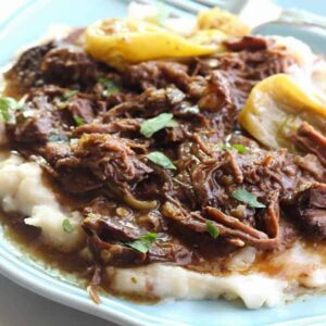 a plate of mashed potatoes with Mississippi Pot Roast on top