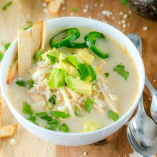 white soup bowl of chicken chili topped with jalapeños and avocado